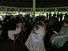 People sit under the site's historic pavilion