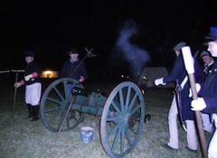 Militia members fire the cannon at night.