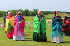 Women in traditional Caddo dress perform a dance.