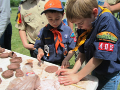 Two boy scouts make pinch pots.
