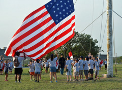 Campers raise an American flag.