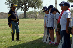Campers stand in line to receive orders from a soldier.