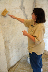 Volunteers uses a brush to apply the whitewash to a wall.