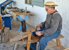 Interpreter sits on the wooden shave horse.