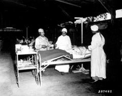 Three nurses attend to a patient in bed.