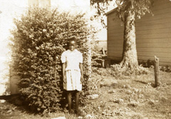 Young girl standing beside cottage.