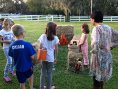Children check out the pumpkin bowling activity