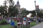 People sitting in folding chairs on the lawn of the Denton courthouse