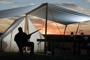 Soldier holds a gun sitting at a tent.