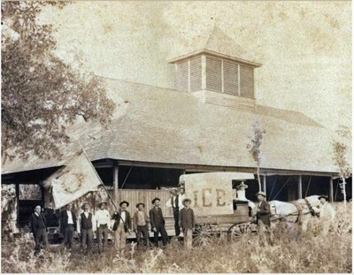Historic photo of people standing in front of brewery with banner waving.