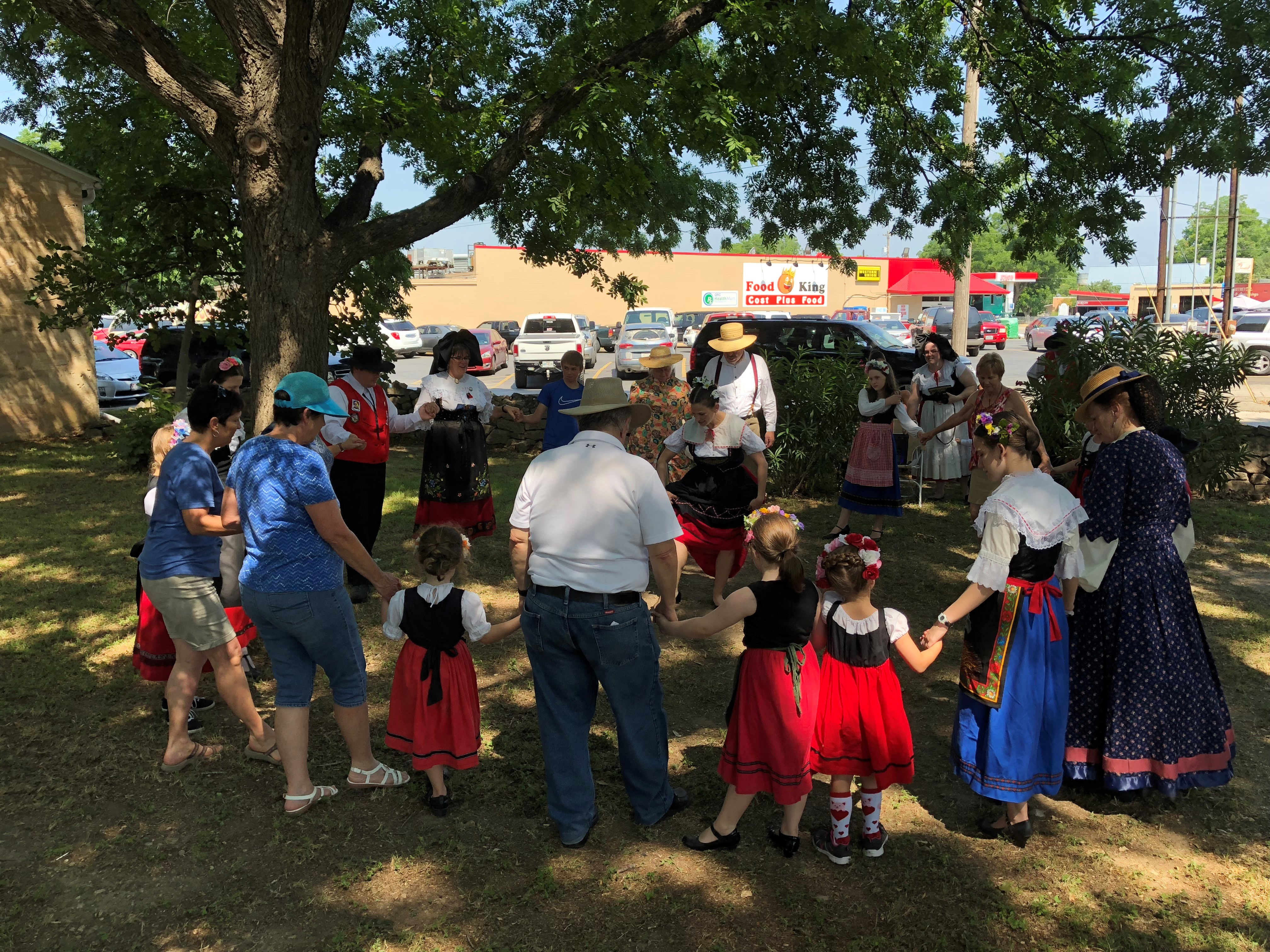 People learning Alsatian dancing in the shade of the grove at Landmark Inn State Historic Site