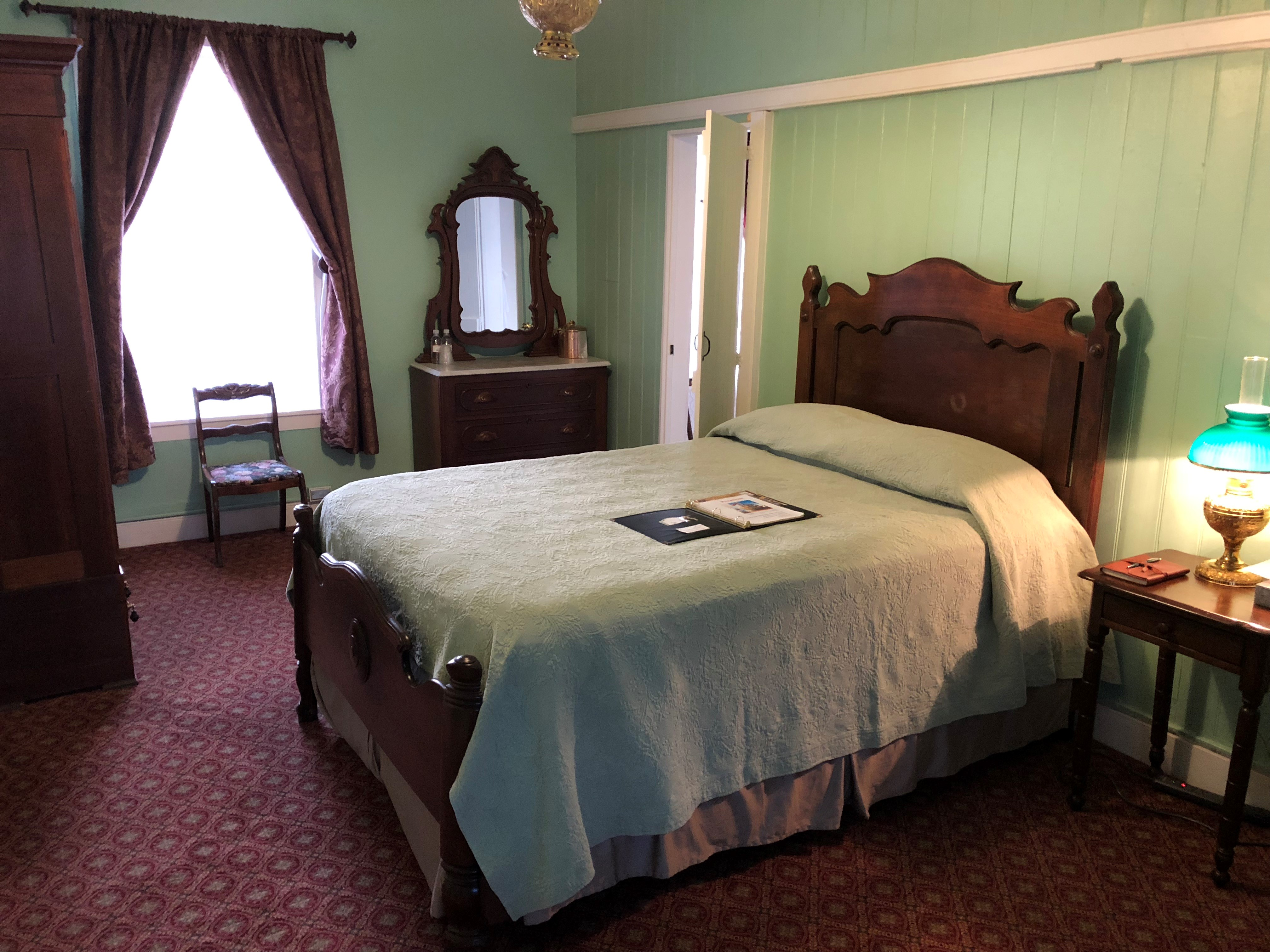Room 4 at the Landmark Inn State Historic Site, reflecting the late 1800s in green, brown, and maroon colors