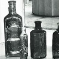 "An old sarsaparilla bottle (left) stands next to a bottle once containing ""teething syrup"" for infants."