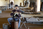 A historical re-enactor polishes his gun in a restored bunkhouse