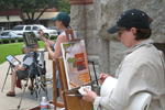 One person sits and two stand while painting views of main street