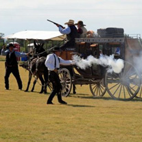 Reenactment with gunfire and stagecoach.
