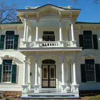 A two story historic home with a large front door and double columns