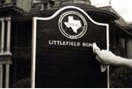 A hand wipes black lacquer off the type and logo on a historical marker in the process of restoration