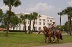 Two men on horseback ride in front of a building and lawn with palm trees