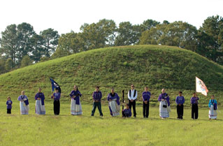 People in historic dress lined up in front of a hill