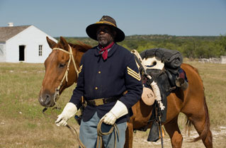 African-American man dressed as a soldier standing with a horse