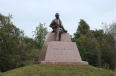 Statue of a man sitting atop a monument