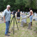 Videographer Curtis Craven, former THC Commissioner Lareatha Clay, and Shankleville resident Chezmin Barnett in the Jim Shankle Cemetery.
