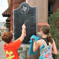 Finn and Avery Taylor refinish a historical marker