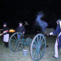 Militia members firing the cannon at night.