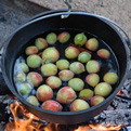 Peaches and cinnamon boiling in a cast iron pot.