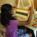 Young girl works at weaving.