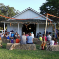 Visitors sit on hay bales to watch the entertainment