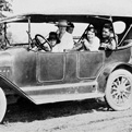 Historic image of people riding in antique car.