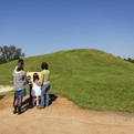 Photo of visitors viewing a ceremonial earthen mound at Caddo Mounds State Historic Site.