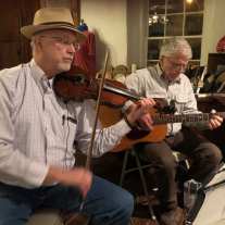 Two men seated, one playing fiddle and the other a guitar