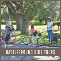 """A family on bikes stands under a tree; text reads """"Battleground Bike Tours"""""""