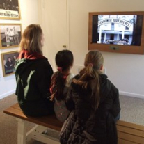 Visitors watch video as part of the new orientation exhibit at the Sam Rayburn House State Historic Site