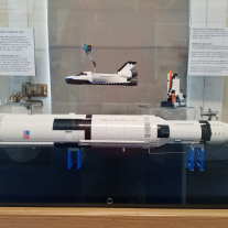The exhibit displays several building toy models of NASA spacecraft.