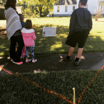 A family takes the self-guided Lost Neighborhood tour, learning about a house that once stood next to the Eisenhower Birthplace house.