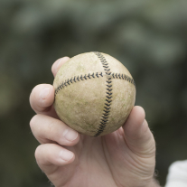 Baseball with stitch pattern in an 'X' held in a right hand