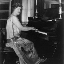 Miss Ima Hogg seated at her piano.