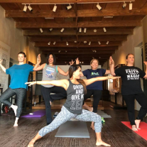 Women in tree and warrior yoga poses in historic museum space