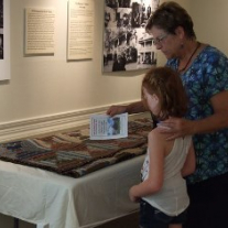 Visitors admire Log Cabin quilt on loan to the Sam Rayburn House from the Varner-Hogg Plantation State Historic Site