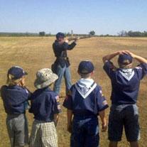 Boy scouts watch rifle demo.