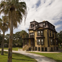 The exterior of Fulton Mansion with palm trees.