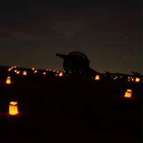 silhouette of a cannon at night surrounded by lights