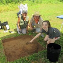 Archeologists pose around a dig.