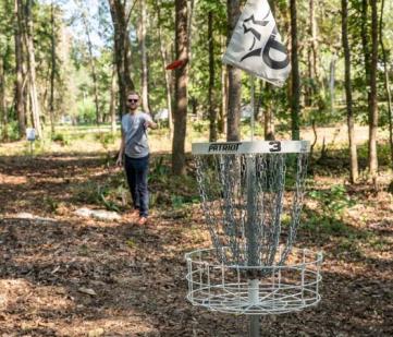 Handsome man plays frisbee golf