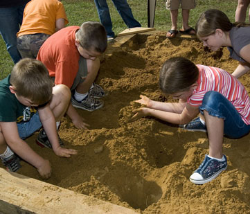 Kids play in a mock archeology dig.