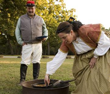 Reenactors prepare food.